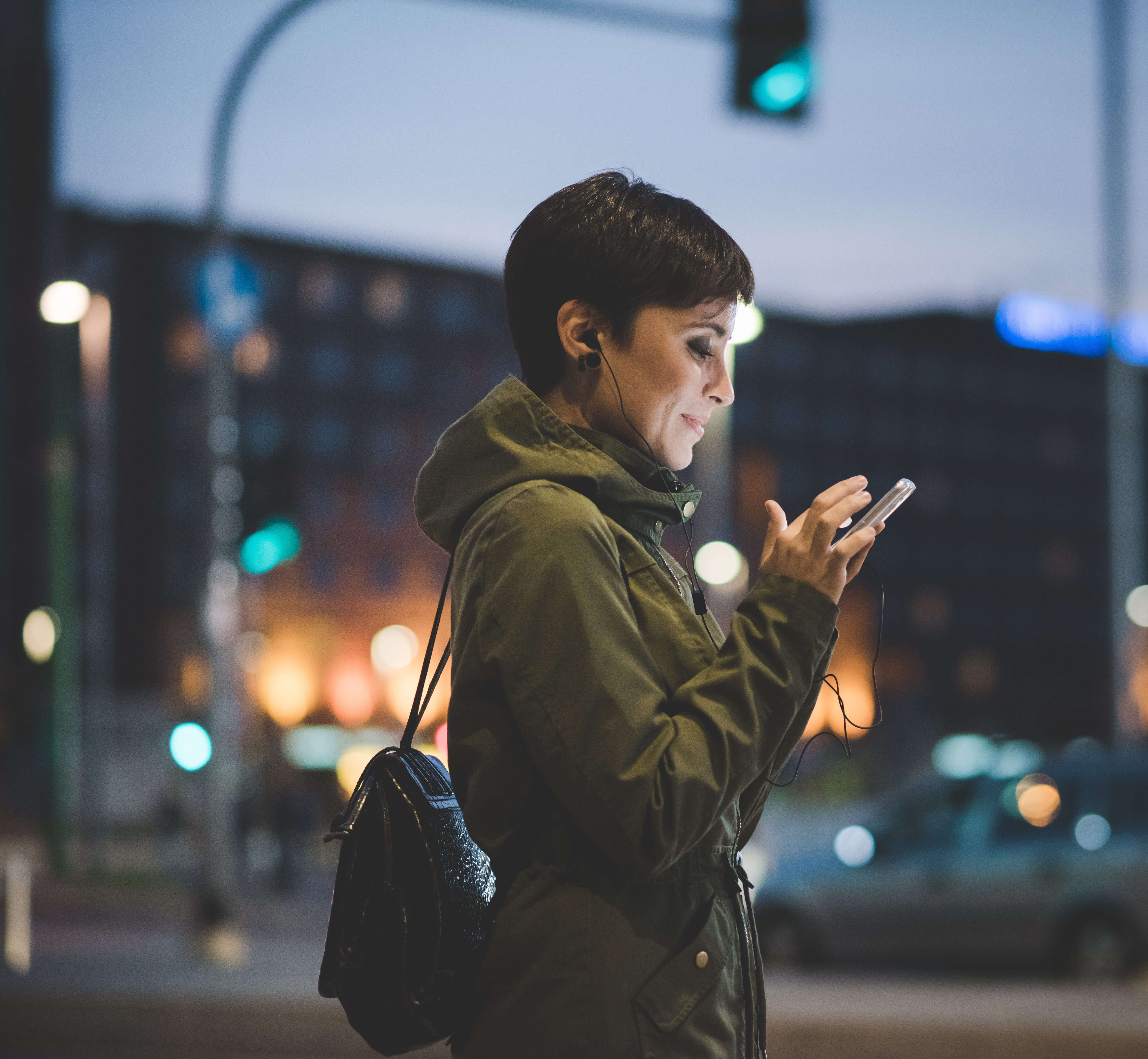 Woman holding a smartphone looking down the screen in city